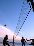 Playing volleyball at sunset. Area is in Sentosa Island, Singapore. The sunset was colourful and these men were having a game of volleyball. Picture was taken to Stock Images