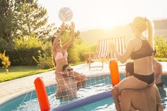Playing volleyball in a swimming pool stock photo