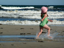 Playing with water. My younger daugter's running on the beach Royalty Free Stock Photos
