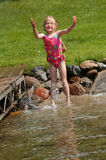 Playing in Water. A young girl enjoys splashing in the water along the shore at her grandparents' cabin on a warm, summer day Stock Photography