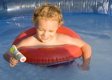 Playing in Water. Young blond boy playing with squirt gun in swimming pool Stock Images
