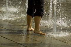 Playing in the Water Fountain. Legs and bare feet of a young person, playing in the cooling spray of a water fountain in Salzburg, Austria Royalty Free Stock Photo