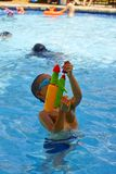 Playing water gun. Little boy shooting water gun in pool, having fun in summer time royalty free stock images