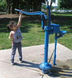 Playing at the Water Pump. A little girl playing at the Water Pump Royalty Free Stock Photo