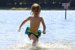 Playing in the water. Young boy running in the shallow water in a lake Royalty Free Stock Images