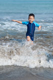 Playing with waves. Children having fun at the beach Stock Photo