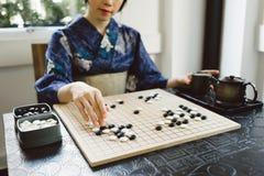 Playing wei qi game. Cropped image of Japanese girl playing wei qi game Stock Image