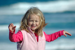 Playing in the wind. A beautiful blond caucasian girl child with happy expression in the pretty smiling face lifting up her white hands playing with the wind Stock Images