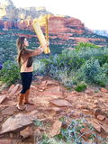 Playing a Wind Harp in Sedona, Arizona. Young Woman holding a wind harp up to a breeze in the red rock area of Sedona, AZ Royalty Free Stock Photography