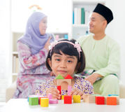 Playing woodblock. Malay girl building a wooden toy house. Southeast Asian family at home. Muslim parents and child living lifestyle stock images