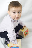 Playing  with wooden boxes. A little child playing with some wooden boxes Royalty Free Stock Photography
