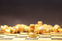 Playing wooden chess. White pawn against the rest of the figures Stock Photography