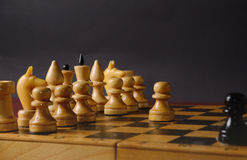 Playing wooden chess. White pawn against the rest of the figures on the board Royalty Free Stock Photography