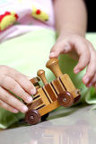 Playing with a wooden train toy. Close up of hands of a little child playing with a wooden train toy Stock Photography