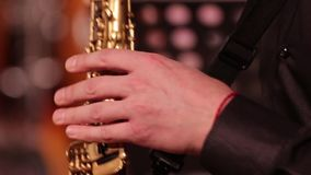 Playing on a wooden wind instrument soprano saxophone. Close-up. The musician retrieves the sounds of music by clamping the keys a. Playing on a wooden wind stock video