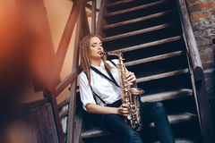 Playing young attractive girl sitting on steps in white shirt with a saxophone - outdoor in old town. young woman with sax Royalty Free Stock Photo