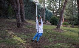 Playing with zip line in the garden. Child playing and sliding on a zip line between two trees in his garden Stock Photography