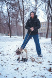 Playingin del perro del dogo francés el invierno con el hombre Imagen de archivo