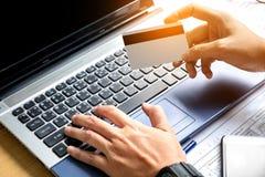 Playments en línea, mano que lleva a cabo pagos con tarjeta de crédito y que usa el La imágenes de archivo libres de regalías