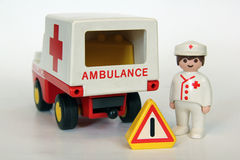 Playmobil - Doctor, ambulance and warning sign. A Playmobil red cross doctor standing besides his ambulance with a warning sign on a white background. Playmobil Royalty Free Stock Photography