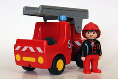 Playmobil - Firefighter with fire engine. A Playmobil firefighter standing near his fire truck on a white background. Playmobil are famous construction toys Stock Photos