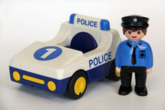 Playmobil - Police officer and car. A Playmobil police officer standing besides his police car on a white background. Playmobil are famous construction toys Royalty Free Stock Photo