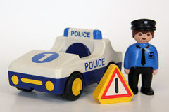 Playmobil - Police officer, car and warning sign. A Playmobil police officer standing besides his police car on a white background, with a warning sign Stock Photos