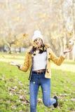 Playng allegro della giovane donna delle foglie nel parco fotografia stock libera da diritti