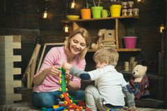 Playroom concept. Playroom is where imagination go wild. Mother and child play with toy bricks in playroom. Mother and royalty free stock photography