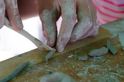 He plays clay with pleasure in the children`s ceramics workshop. royalty free stock photos