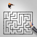 She plays her success music. Top view of businesswoman playing violin and drawn labyrinth on floor stock photo