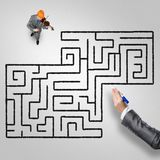 He plays his success music. Top view of businessman playing violin and drawn labyrinth on floor stock photo