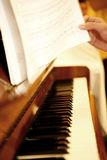 Plays on piano. Reading the notes in frond of piano Royalty Free Stock Photo