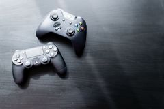 Xbox and Playstation controller sat next to each other on a dark background stock photo