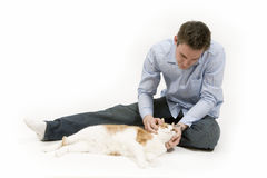 Playtime. Young man spends time playing with his pet cat stock image