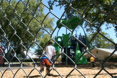 Playtime behind the fence. Young children playing in a playground as seen from behind a fence Royalty Free Stock Images