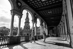 Plaza de Espana in Seville, Andalusia. Seville, Spain - September 19, 2015: Tourists walking inside the corridors of the Plaza de España in Seville, Spain, a Stock Image