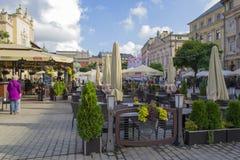 Plaza del mercado con los cafés y los restaurantes en la ciudad vieja de Kraków Imágenes de archivo libres de regalías