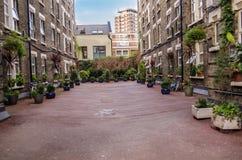 Plaza maravillosamente ajardinada entre los edificios en la ciudad Foto de archivo libre de regalías
