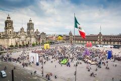 Plaza principal Zocalo con la catedral, el palacio nacional y la bandera mexicana grande en el centro imagen de archivo
