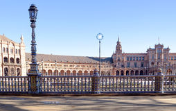 Plaza of Spain in Seville. View from one of ceramic railings with lamp post, are several bridges, the lake with reflections and the background the Catholic Stock Image