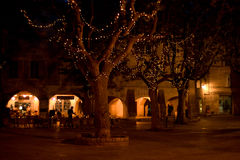 Plaza in Uzes France by night. Bars and restaurants spill out onto the central plaza in the medieval town of Uzes in Lanuedoc France. Originally a Roman city Stock Image