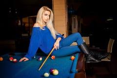 Plciowa blondynki dama pozuje na bilardowym stole z wskazówką obraz stock