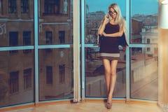 Plciowa dama opowiada telefon okno z miasto widokami zdjęcie stock