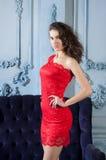 Plciowa dziewczyna w czerwieni sukni blisko zgłębia błękitną kanapę Obraz Stock