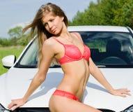 Plciowa dziewczyna w różowym bikini z biały samochodem Obrazy Stock
