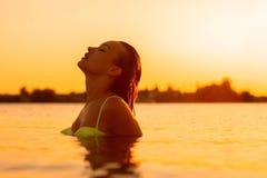 Plciowa młoda dama w morzu przy ciepłym zmierzchem zdjęcie royalty free