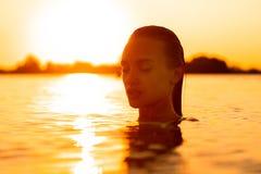 Plciowa młoda dama w morzu przy ciepłym zmierzchem obraz stock