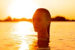Plciowa młoda dama w morzu przy ciepłym zmierzchem fotografia royalty free