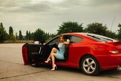 Plciowa młoda kobieta na szpilkach w czerwonym samochodzie obrazy stock